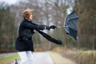 11437639-a-young-woman-is-fighting-against-the-storm-with-her-umbrella